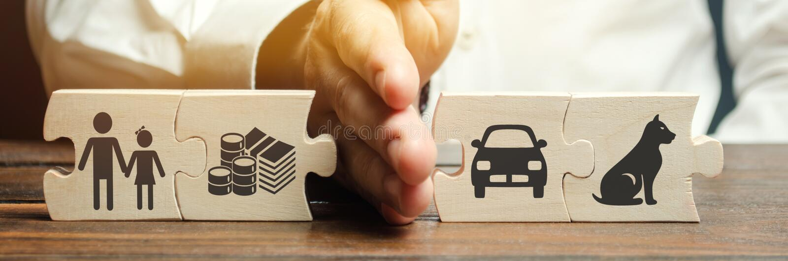 A man shares wooden puzzles with images of property, children and pets. The concept of divorce. The process of sharing property. Child custody and parental stock photography