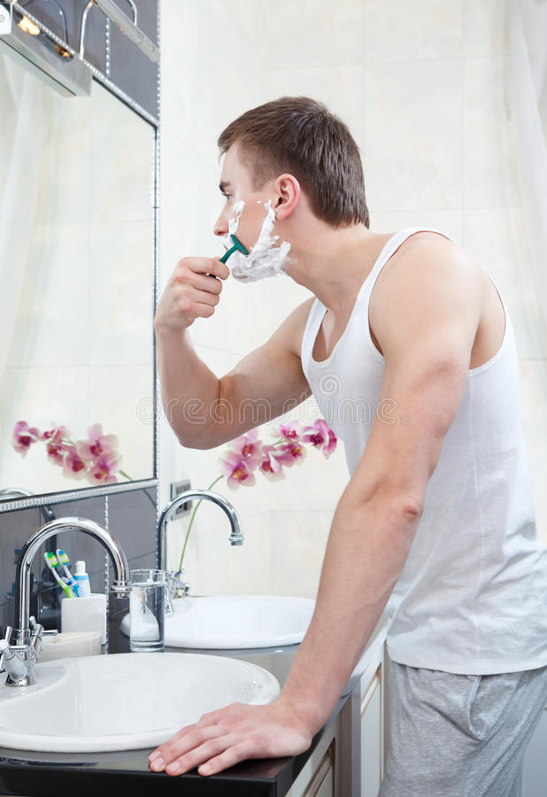 Man shaves in the bathroom stock image