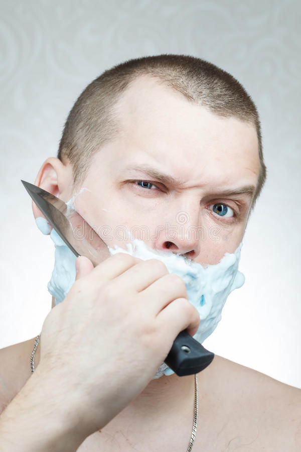 Man shaves his beard a large knife royalty free stock images