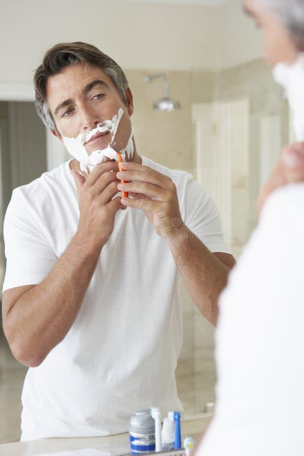 Man Shaving In Bathroom Mirror royalty free stock image
