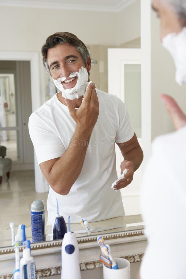 Man Shaving In Bathroom Mirror stock photos
