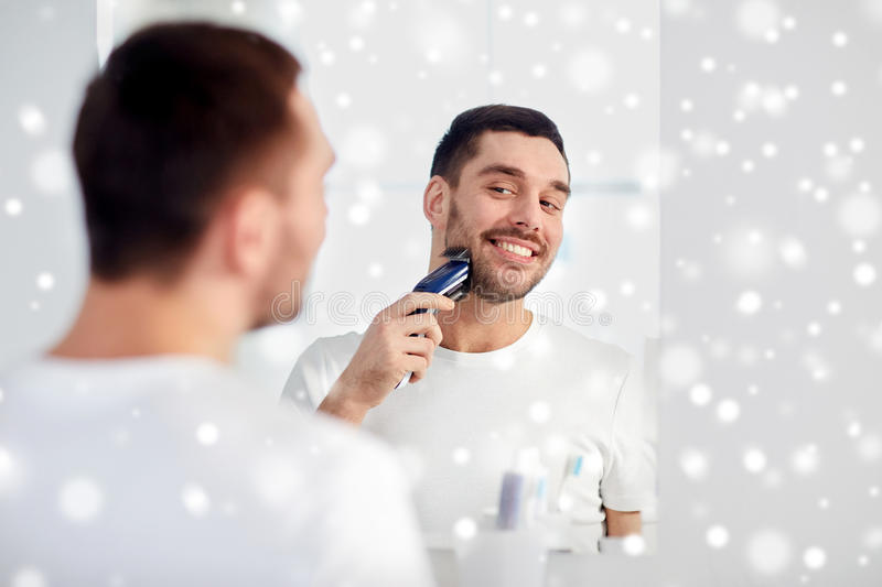 Man shaving beard with trimmer at bathroom. Beauty, shaving, grooming and people concept - young man looking to mirror and shaving beard with trimmer or electric stock photo