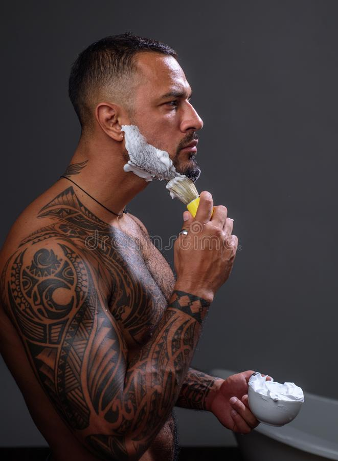 Man shaving. Feeling fresh after shaving. brutal sportsman washing in bath. steroids. sport and fitness, health royalty free stock image