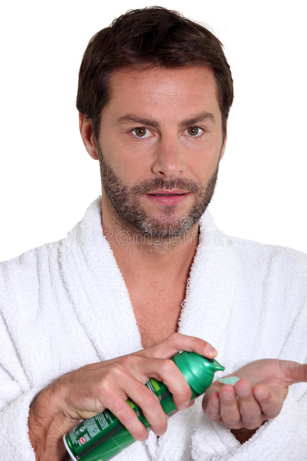 Man with shaving foam. Man spraying shaving foam into hand stock photography