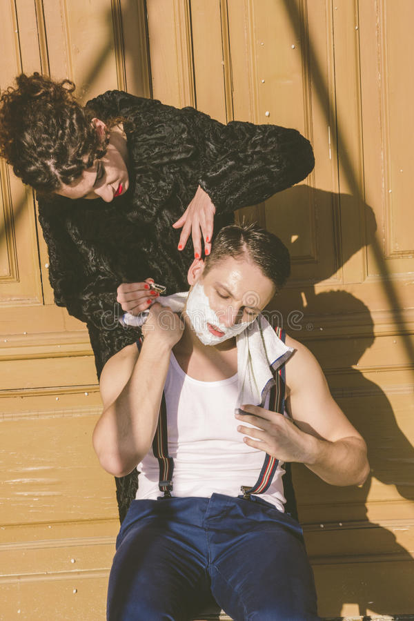 Man with shaving foam on his face and towel around his neck siting on chair and posing while pretty women shave him. Handsome man with shaving foam on his face royalty free stock photos