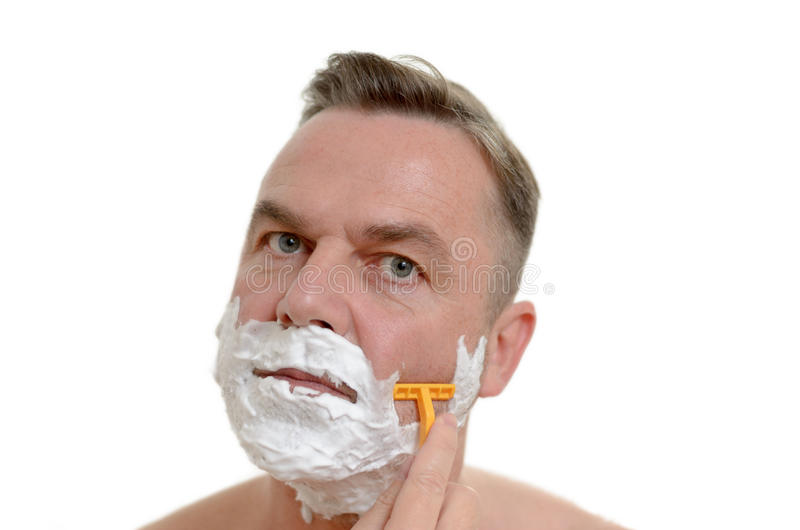 Man shaving his beard with a razor and lather. Middle-aged man shaving his beard with a razor and lather from shaving cream covering his face, isolated on white stock photography