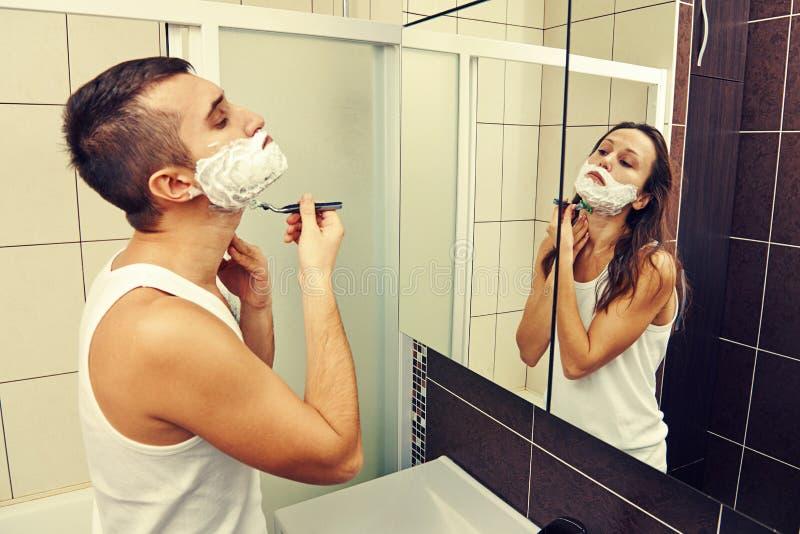Man shaving and looking at a woman. Young men shaving and looking at a women in the mirror stock photos