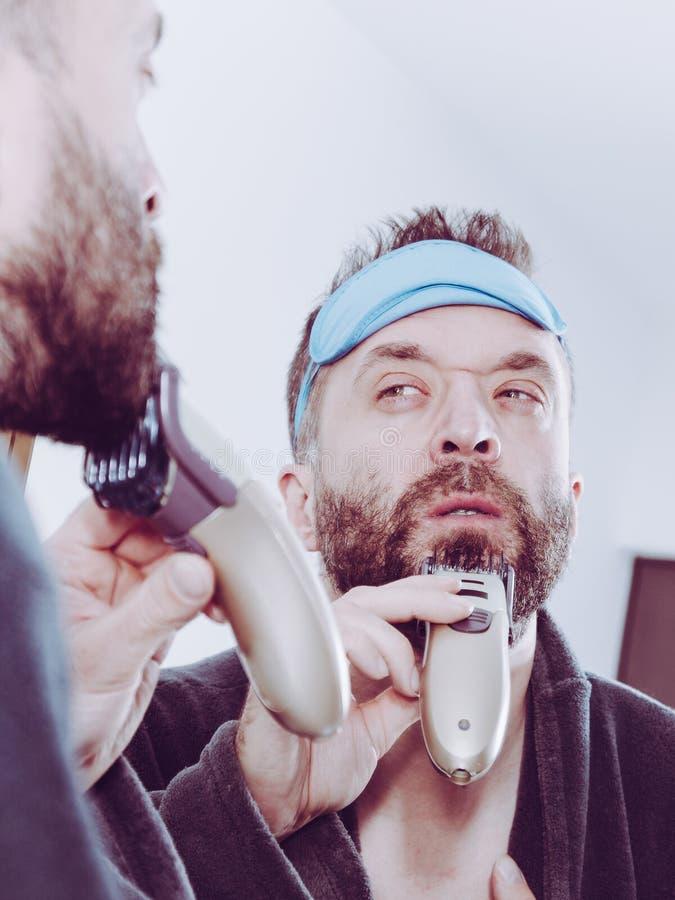 Man shaving trimming his beard stock images