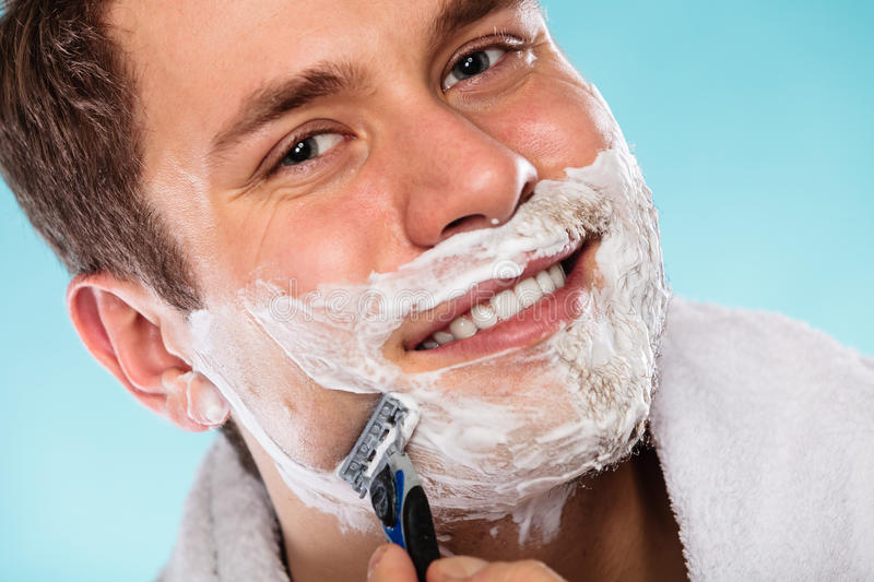 Man shaving using razor with cream foam. Handsome guy removing face beard hair. Skin care and hygiene royalty free stock image