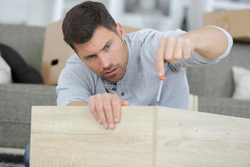 Man in shirt assemble furniture. Assembling royalty free stock images