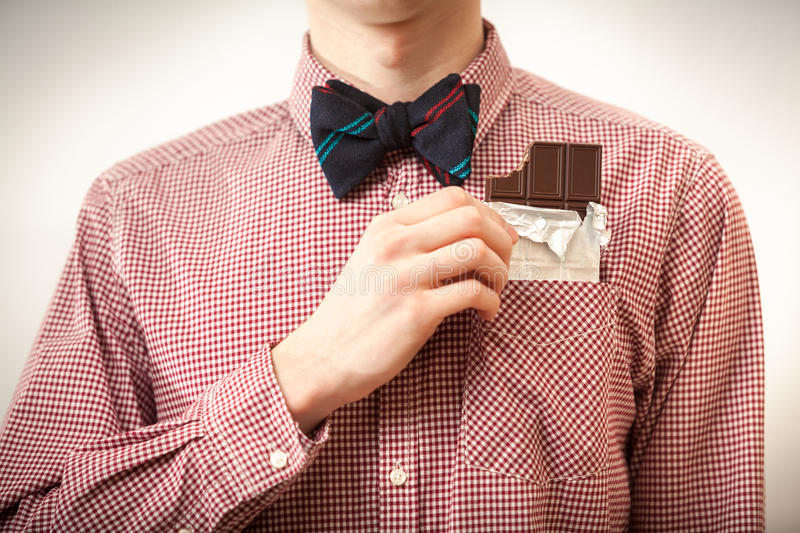 Man in shirt and bow tie taking chocolate out of breast-pocket stock image