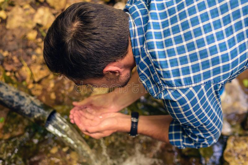 A man in a shirt in a cage collects fresh water from a spring in folded hands, drink water from a source royalty free stock photos