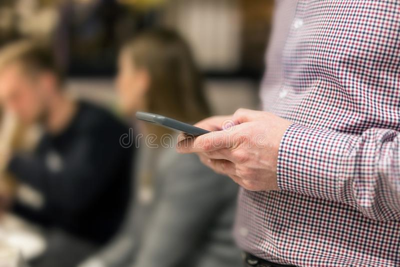 Man in shirt holding smartphone in hand. Businesman using phone during corporate meeting royalty free stock photography