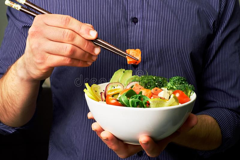 man in a shirt holds poke bowl with salmon, avocado, cucumbers, arugula, broccoli, rice, carrots, cheese and chuha with chopsticks royalty free stock image