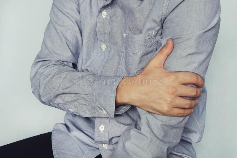 A man in a shirt holds on to the shoulder, arm, wrist, forearm, sports injury, experiencing pain, on a blue background royalty free stock images