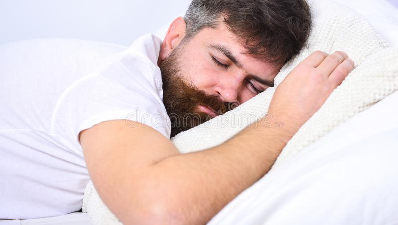Man in shirt laying on bed, white wall on background. Macho with beard and mustache sleeping, relaxing, having nap, rest. Nap and siesta concept. Guy on calm stock photos