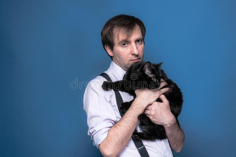 Man in shirt and suspender holding and hugging black funny cat stock photos