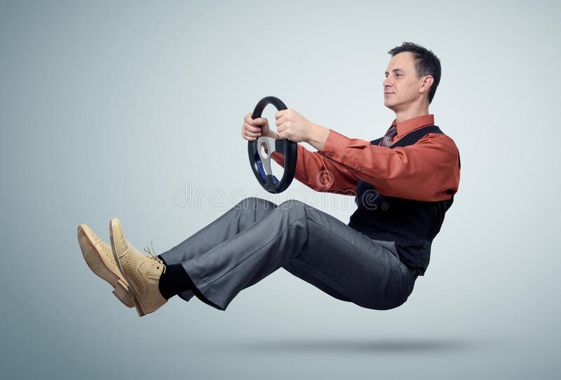 Man in a shirt and tie car driver with a steering wheel. On background royalty free stock image