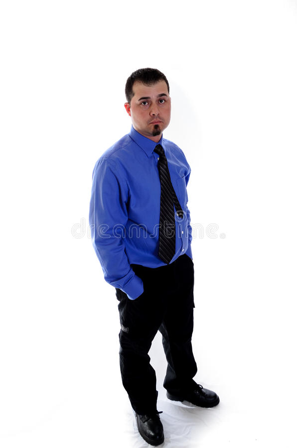 Man in shirt and tie looking at you. hands in pockets. A business man in blue shirt and tie looking at you with hands in pockets stock image