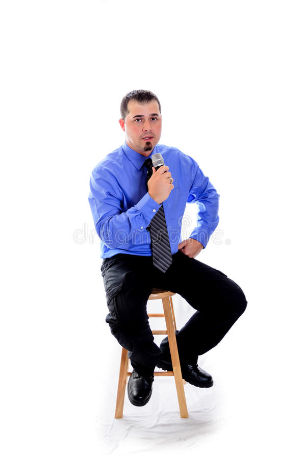 Man in shirt and tie speaking into microphone. A businessman in a shirt and tie speaking into a microphone. Sitting on a stool stock image