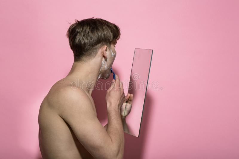 Man shirtless shave bearded face with razor at mirror stock image