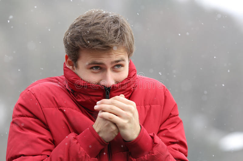 Man shivering in cold winter. And rubbing hands while is snowing stock image