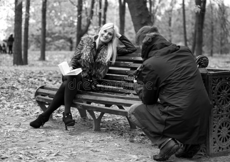 A man shooting young attractive woman sitting on the bench in autumn park, black and white photo. 2017.10.21, Moscow, Russia. A man shooting young attractive stock image