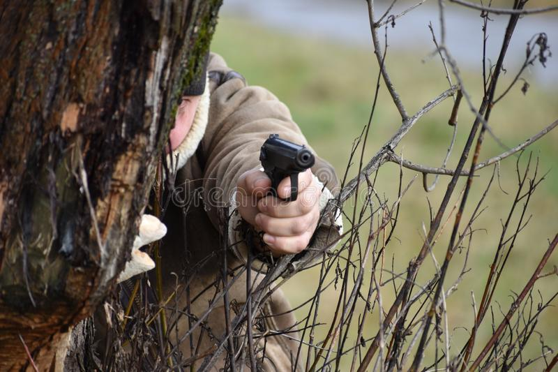 Man shoots from behind a tree. Killer in the forest. A man with a gun. The hit man is waiting for the victim. Murder in the forest stock image