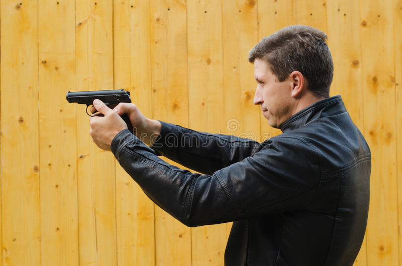 The man shoots from a pistol. The man in a black leather jacket shoots from a pistol stock photography