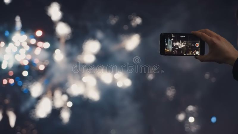 A man shoots a selfie video of a festive pyrotechnic show in a night city. A man shoots a video of a festive pyrotechnic show in a night city stock photography