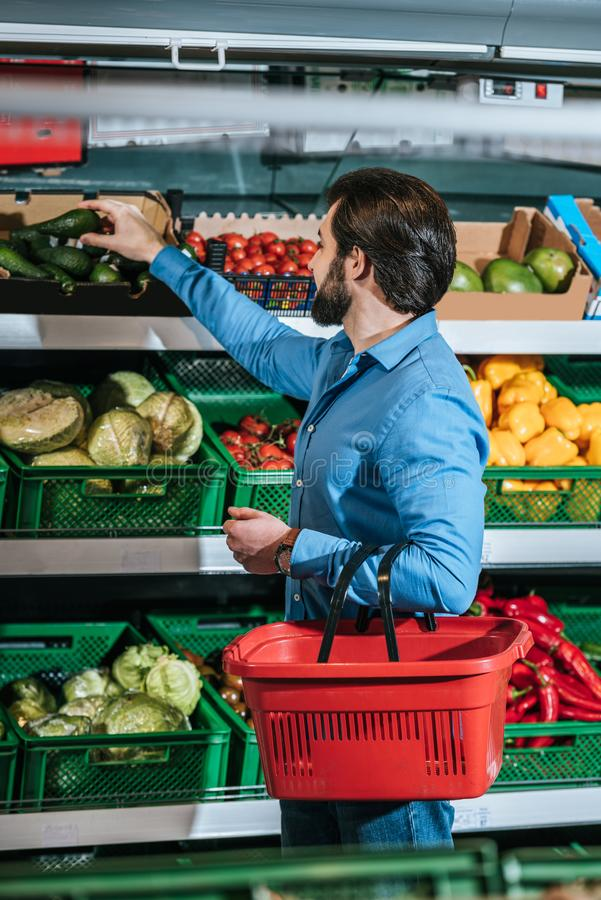 man with shopping basket choosing fresh vegetables royalty free stock photo