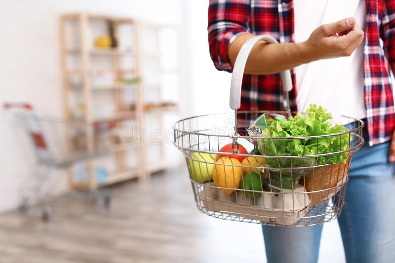 Man with shopping  full of products in grocery store, closeup. Man with shopping basket full of products in grocery store, closeup stock images