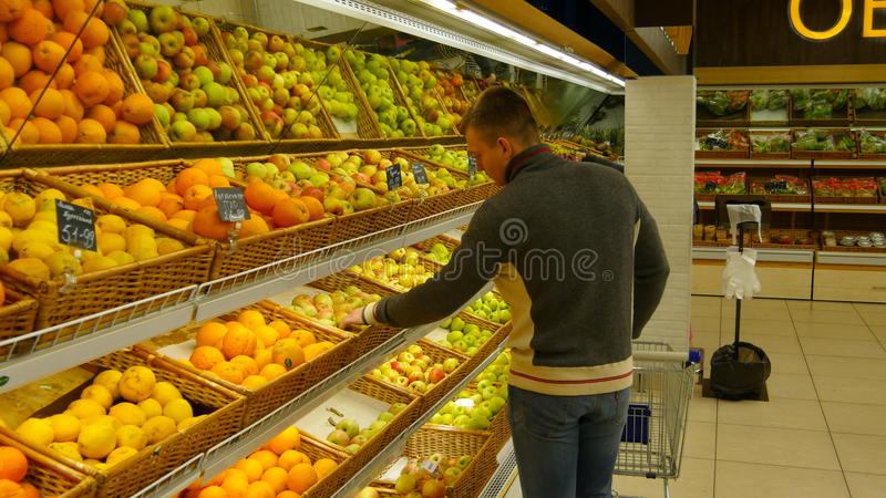 Man with shopping cart choose oranges in the hypermarket.  royalty free stock photos