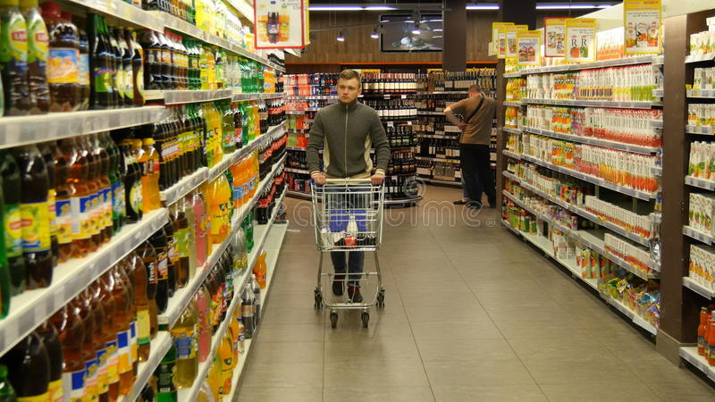 Man with shopping cart walking in the hypermarket.  royalty free stock photos