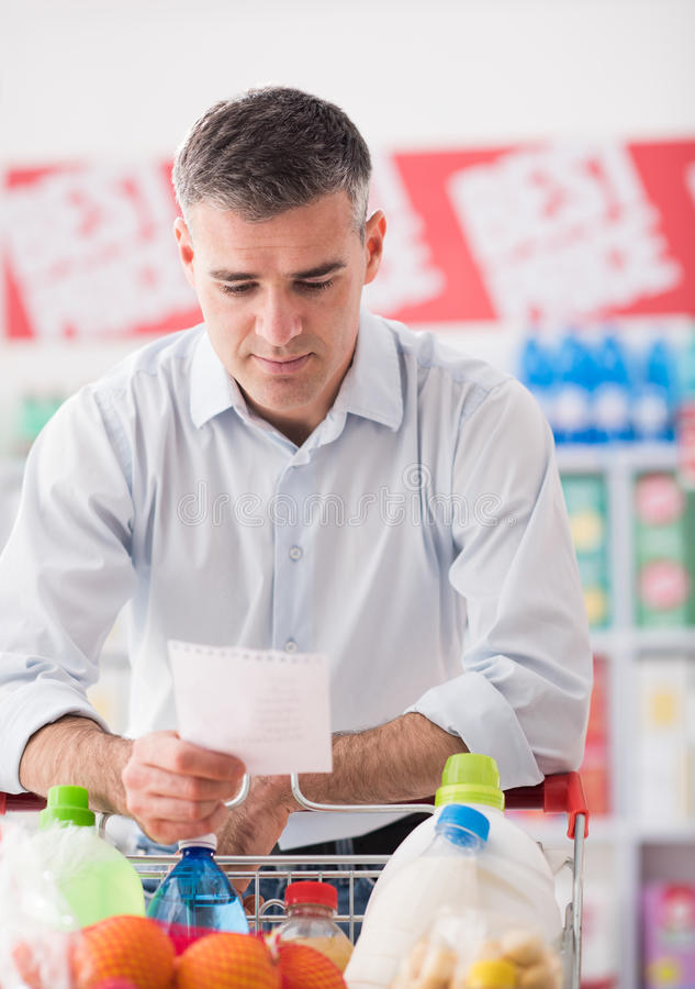 Man shopping with a grocery list. Man at the supermarket shopping with a grocery list and pushing a full cart, lifestyle and retail concept royalty free stock photography
