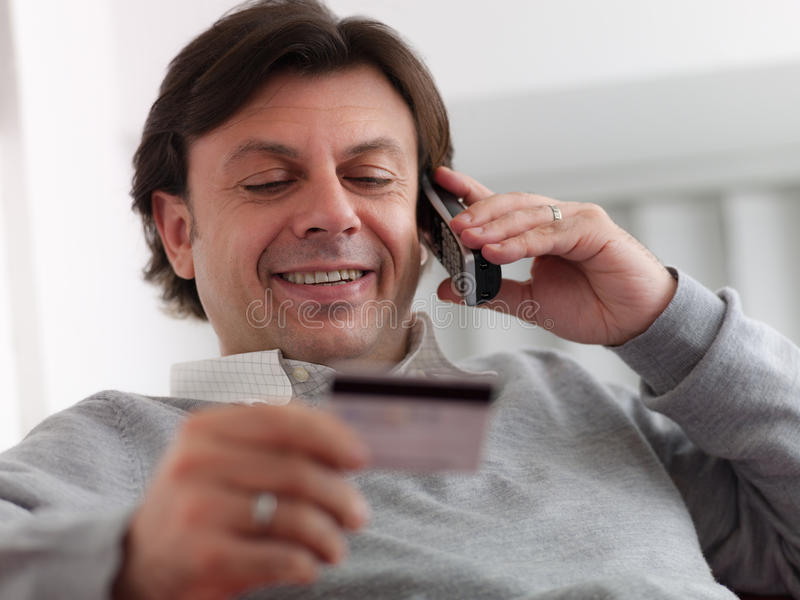 Man shopping from home with credit card. Portrait of happy caucasian middle aged man sitting on sofa, talking on cordless and buying with credit card royalty free stock photos
