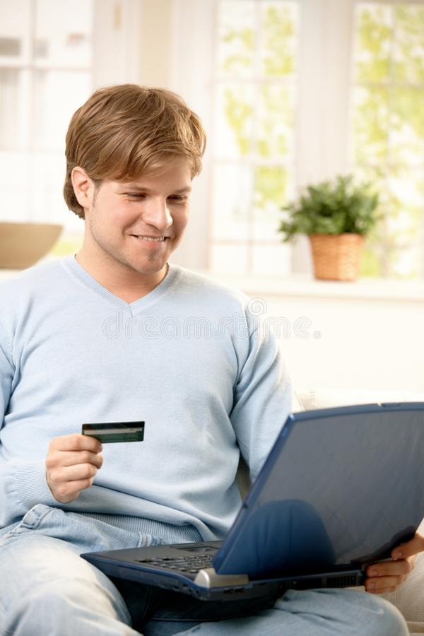 Man shopping online. Smiling man shopping online with laptop computer in lap, holding credit card royalty free stock images