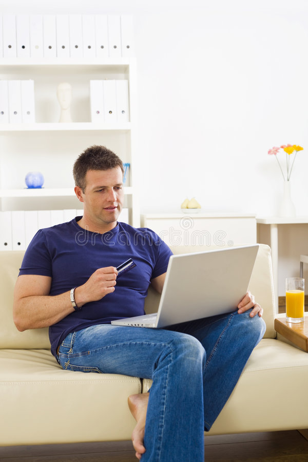 Man shopping online. From home using credit card and laptop royalty free stock photos