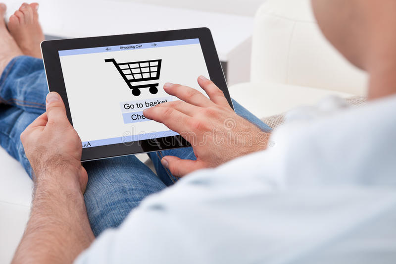 Man shopping online. Close-up Of Man Shopping Online With Digital Tablet
