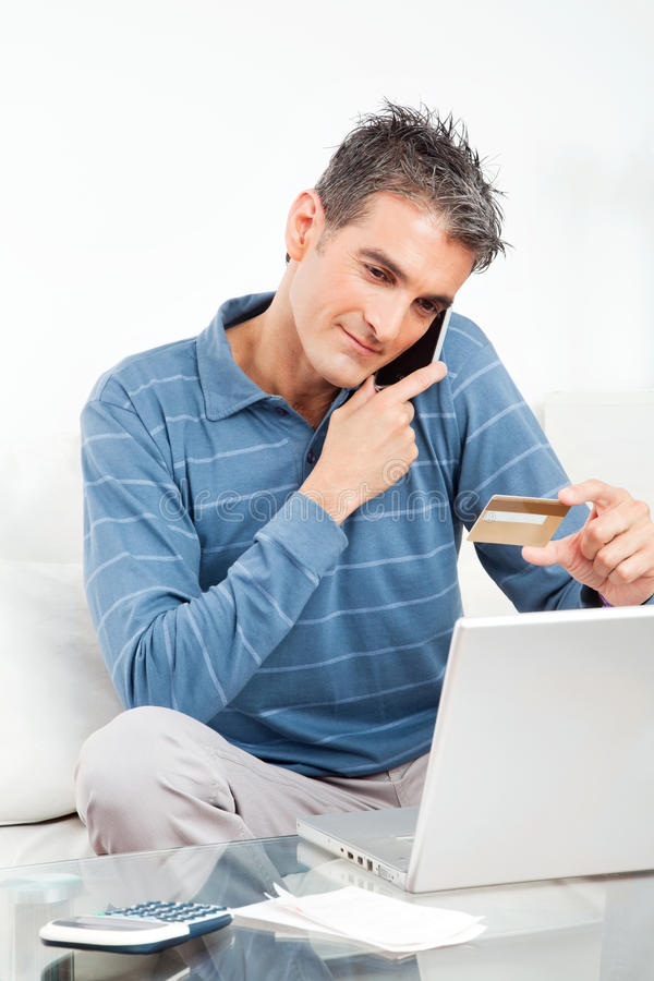 Man shopping online with credit. Card and cell phone royalty free stock images