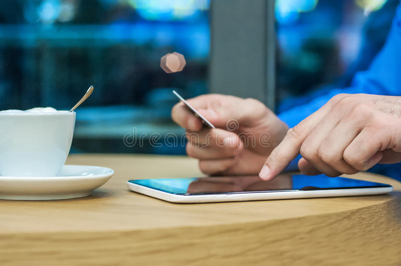 Man shopping using tablet pc and credit card indoor close-up. Young man holding tablet pc and credit card.indoor stock photo