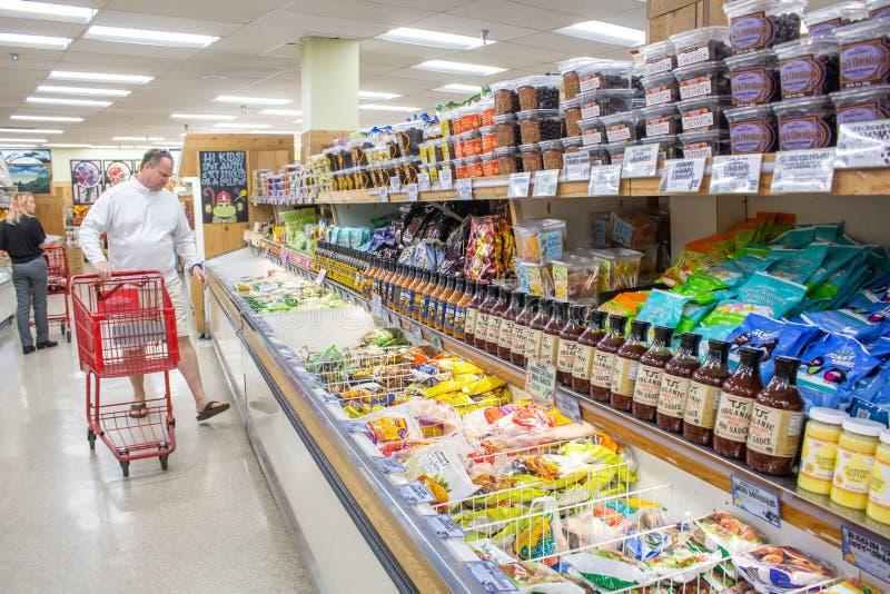 A man shops at Trader Joe`s. A man shops groceries at Trader Joe`s in the freezer section royalty free stock photos