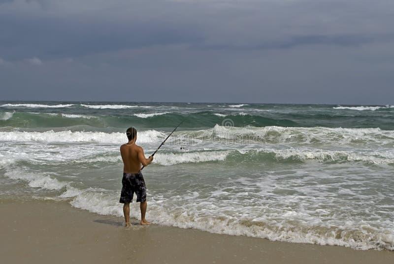 Man shore fishing during storm royalty free stock photo