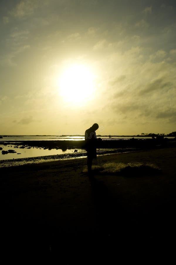 Man on shoreline at sunrise royalty free stock image