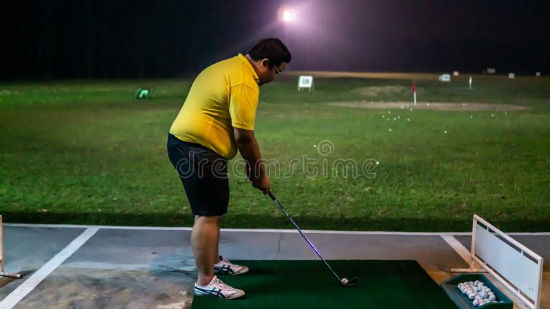 A man with a short pants holding a golf club playing at the golf driving range on a green carpet mat during the night royalty free stock photo