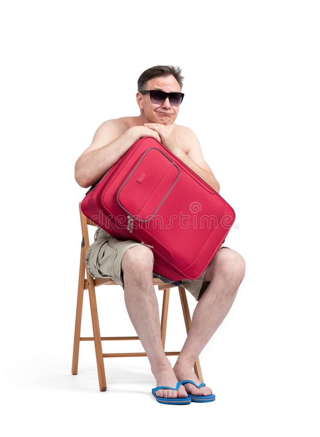 Man in shorts and sunglasses sits on a chair with his hands hugging a red suitcase, waiting. Isolated on white background stock photo