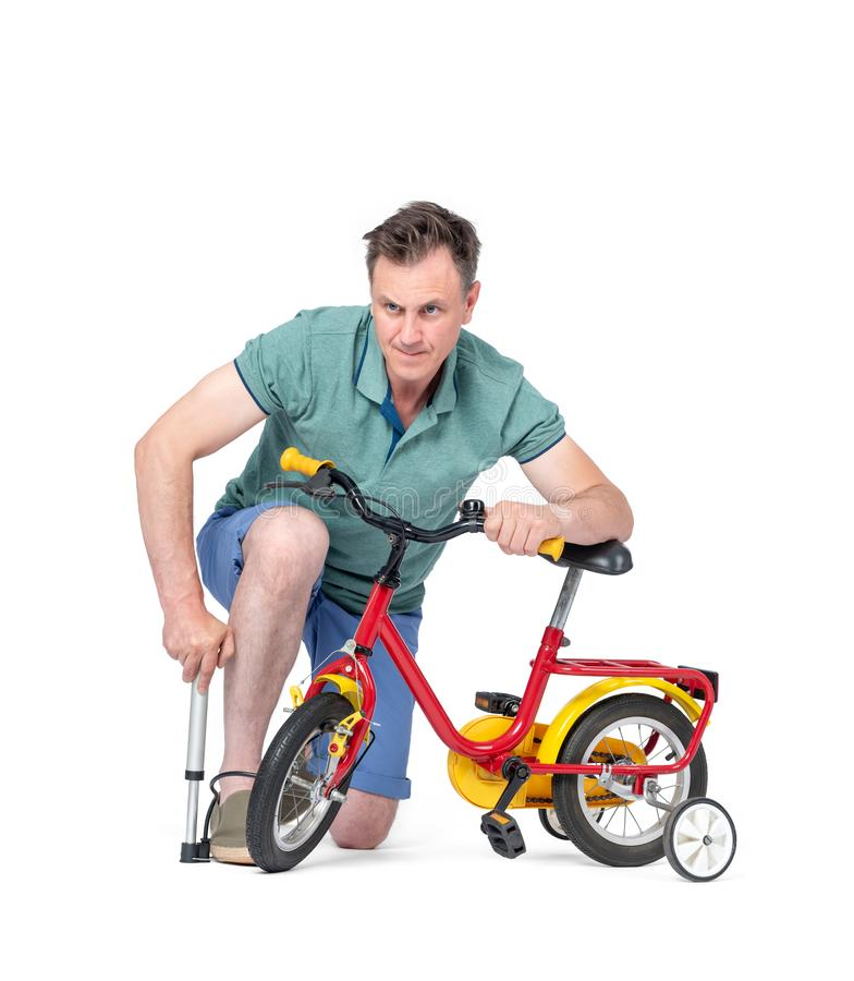 Man in shorts and a t-shirt pumping wheel at children`s bike. Isolated on white background. stock images