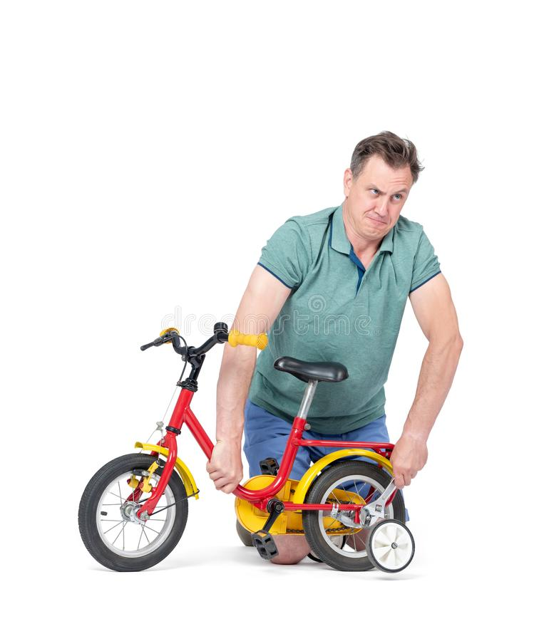 Man in shorts and a t-shirt is repairing a children`s bicycle, in the hands of a wrench. Isolated on white background. royalty free stock photography