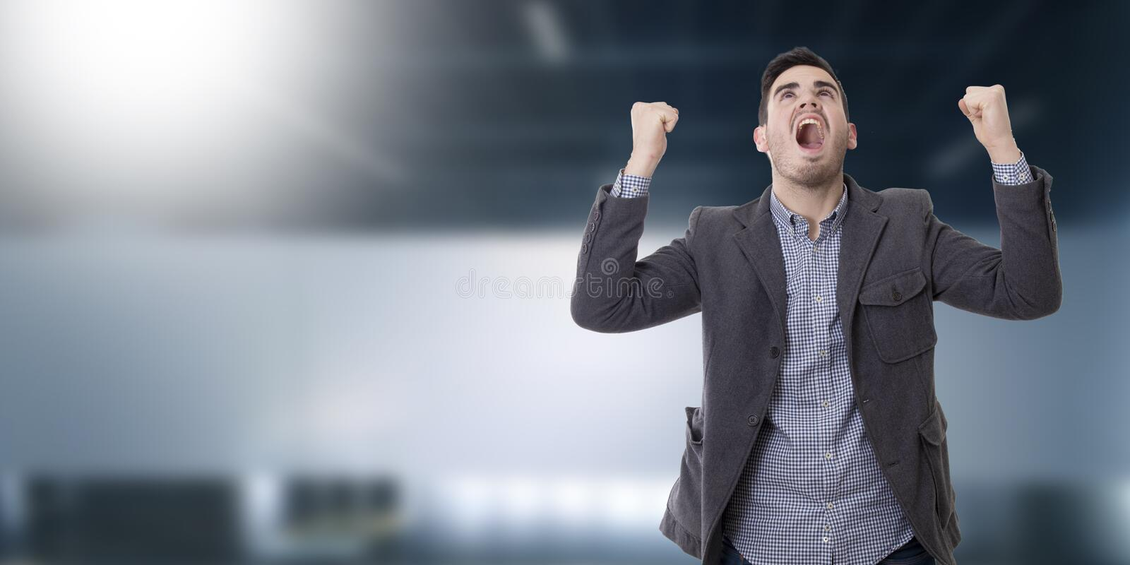 Man shouting enraged. Adult young man shouting enraged with the arms raised stock photos