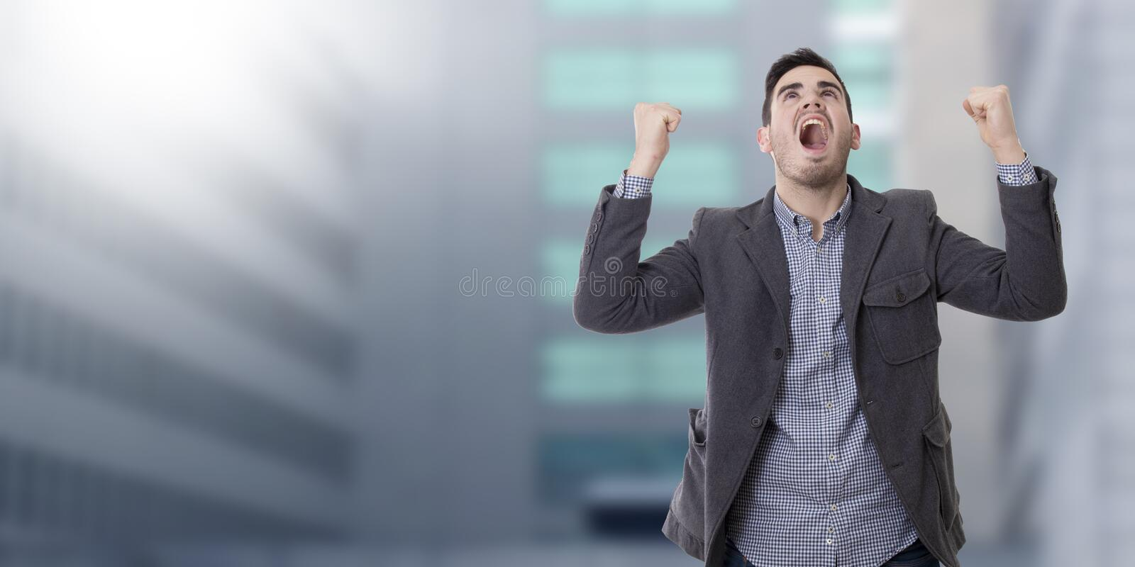 Man shouting enraged. Adult young man shouting enraged with the arms raised royalty free stock image